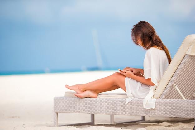 Jonge vrouw op ligstoel met mobiele telefoon op het strand