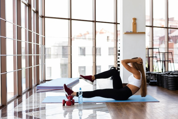 Jonge vrouw op mat uit te oefenen