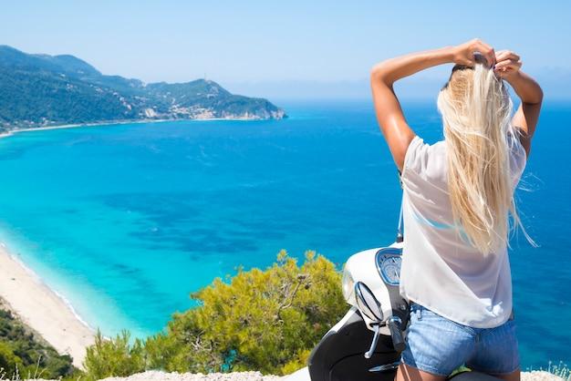 Jonge vrouw op motorfiets aan zee genieten van het uitzicht op het strand