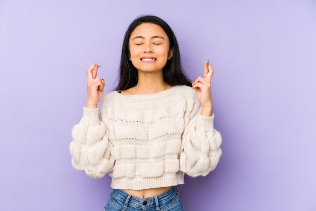 Jonge vrouw op paarse kruisende vingers voor het hebben van geluk