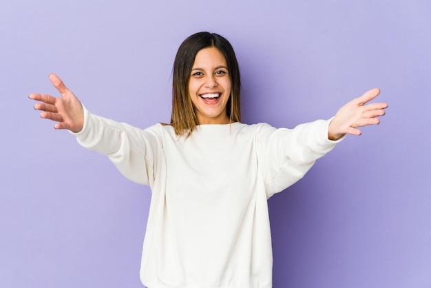 Jonge vrouw op paarse muur voelt zich zelfverzekerd een knuffel geven