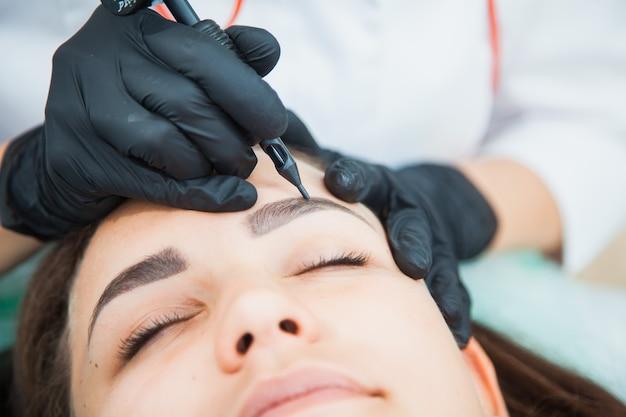 Jonge vrouw op permanente make-up procedure, wenkbrauwen tatoeëren in natuurlijke tint. wenkbrauwcorrectie close-up.