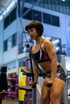Jonge vrouw op sportschool doet triceps pushdown met touw