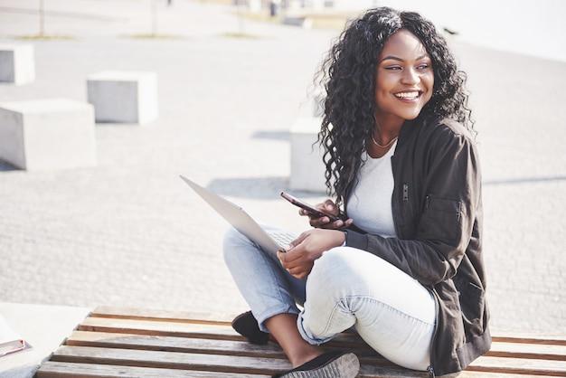 Jonge vrouw op straat die aan laptop werkt en op mobiele telefoon spreekt