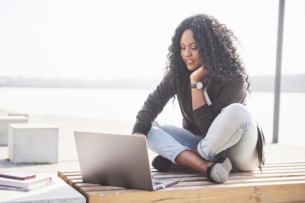 Jonge vrouw op straat die aan laptop werkt