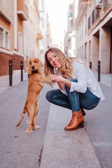 Jonge vrouw op straat haar schattige cocker hond knuffelen. levensstijl buiten met huisdieren