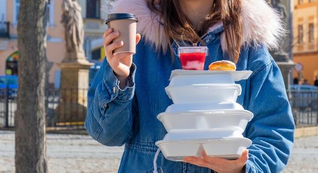 Jonge vrouw op straat met een jas aan met lunchboxen en bezorging van koffie en eten.