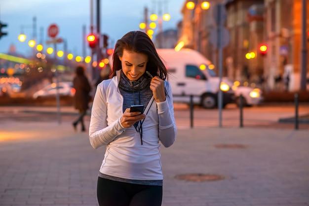 Jonge vrouw op straat met een telefoon