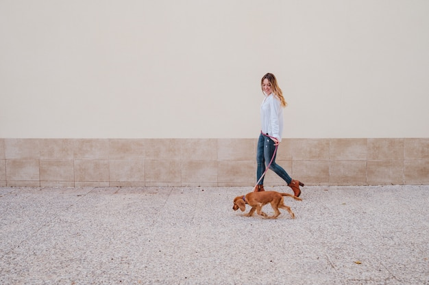 Jonge vrouw op straat wandelen met haar schattige cocker hond. levensstijl buiten met huisdieren