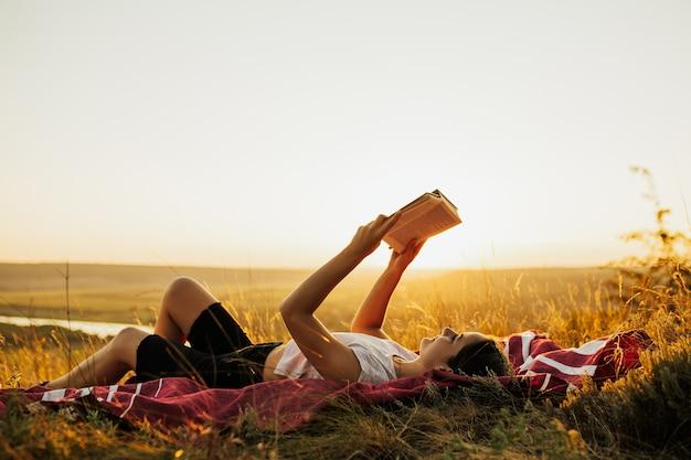 Jonge vrouw op vakantie leest boek op een heuvel bij zonsondergang.