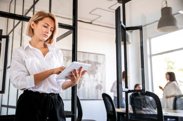 Jonge vrouw op vergadering met behulp van tablet