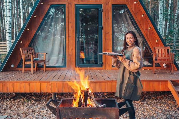 Jonge vrouw op warme herfst dag grill buitenshuis