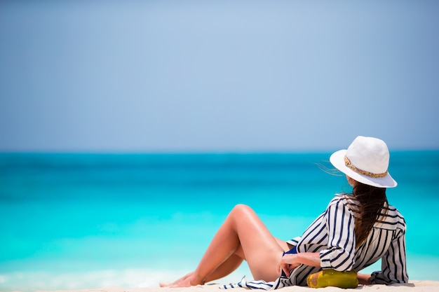 Jonge vrouw op wit strand met kokosnoot