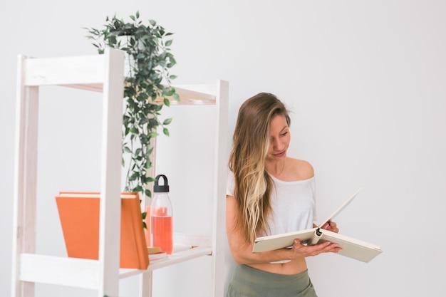 Jonge vrouw op zoek naar fotoalbum thuis herinneringen en vrije tijd concept