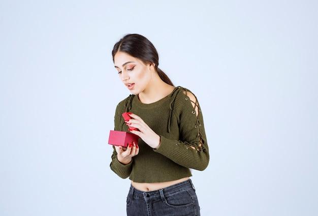 Jonge vrouw op zoek naar geschenkdoos op witte achtergrond.