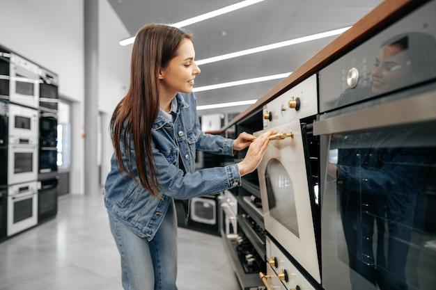 Jonge vrouw op zoek naar nieuwe elektrische oven in een winkelcentrum