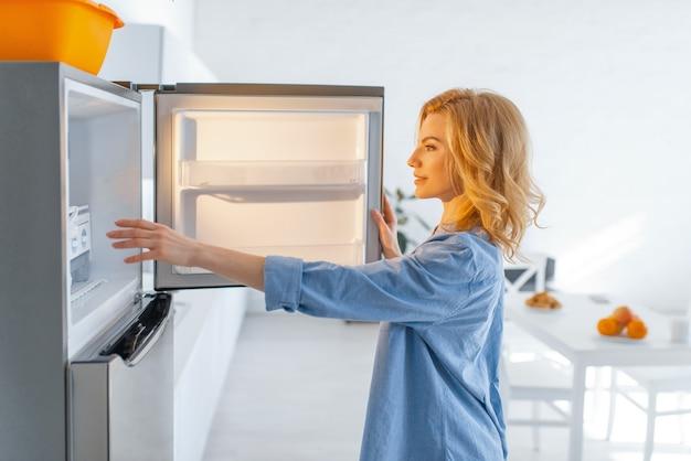 Jonge vrouw opende de koelkast in de keuken.