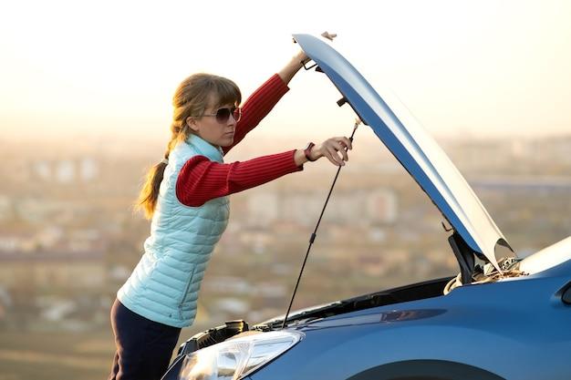 Jonge vrouw openen motorkap van afgebroken auto problemen met haar voertuig.