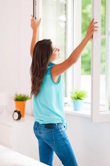 Jonge vrouw opening venster in de woonkamer