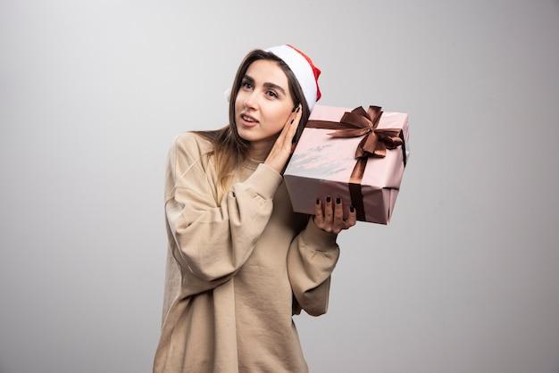 Jonge vrouw opgewonden over een kerstcadeau.