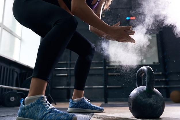 Jonge vrouw opheffen kettlebells in crossfit gym