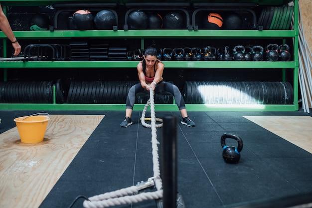 Jonge vrouw opleiding met strijdtouw in een crossfitgymnastiek