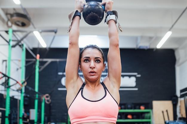 Jonge vrouw opleiding swingende kettlebell binnen in een crossfitgymnastiek