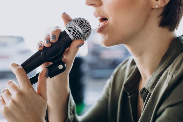 Jonge vrouw opname stem acteren in de studio Gratis Foto