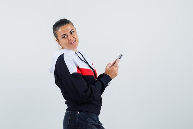 Jonge vrouw opzij kijken terwijl telefoon in kleurrijke sweatshirt vooraanzicht.