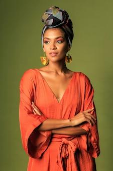Jonge vrouw oranje jurk met tulband en etnische sieraden dragen