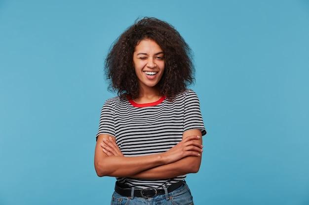 Jonge vrouw over blauwe muur die gestripte t-shirt draagt die met gelukkig gezicht het knipogen glimlachen