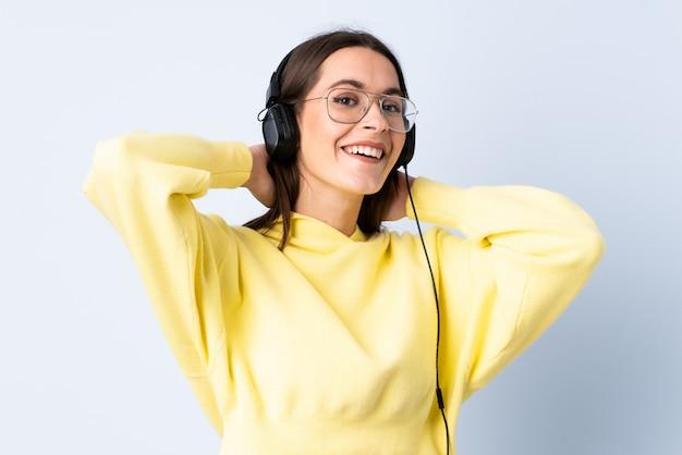 Jonge vrouw over blauwe muur luisteren muziek