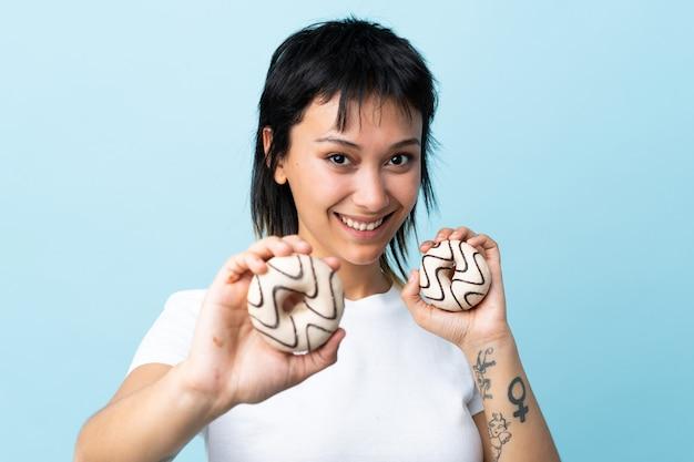 Jonge vrouw over blauwe muurholding donuts met gelukkige uitdrukking