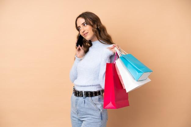 Jonge vrouw over de muur met boodschappentassen en het bellen van een vriend met haar mobiele telefoon