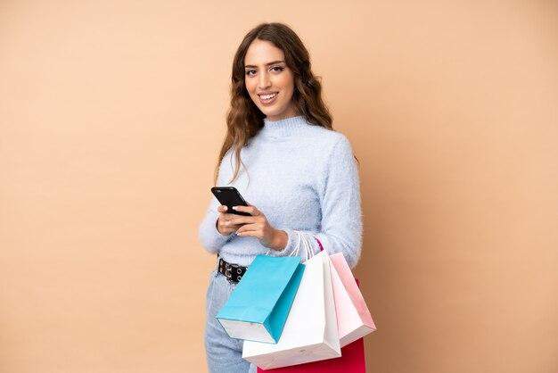 Jonge vrouw over de muur met boodschappentassen en het schrijven van een bericht met haar mobiele telefoon naar een vriend