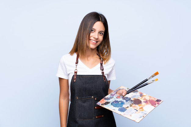 Jonge vrouw over geïsoleerd blauw dat een palet houdt