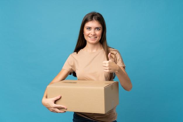 Jonge vrouw over geïsoleerd blauw die een doos houden om het naar een andere plaats met omhoog duim te verplaatsen
