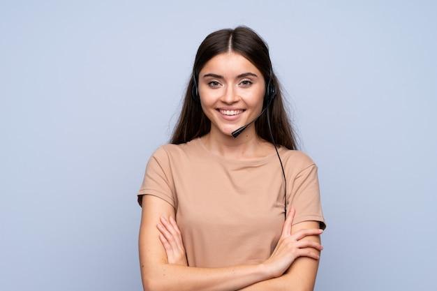 Jonge vrouw over geïsoleerd blauw die met hoofdtelefoon werkt