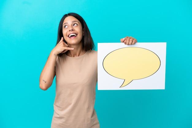 Jonge vrouw over geïsoleerde achtergrond die een plakkaat met het pictogram van de toespraakbel houdt en telefoongebaar doet