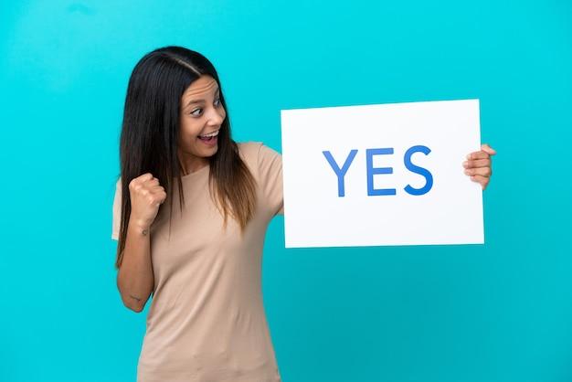 Jonge vrouw over geïsoleerde achtergrond die een plakkaat met tekst ja houdt en een overwinning viert