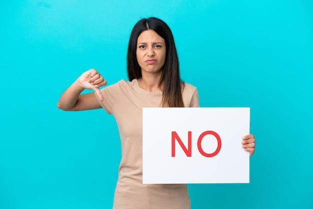 Jonge vrouw over geïsoleerde achtergrond die een plakkaat met tekst nee houdt en slecht signaal doet