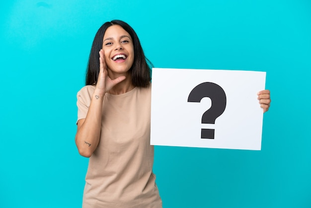 Jonge vrouw over geïsoleerde achtergrond die een plakkaat met vraagtekensymbool houdt en schreeuwt