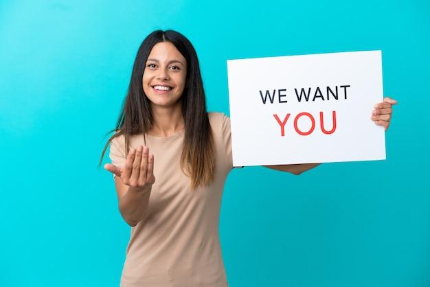 Jonge vrouw over geïsoleerde achtergrond die we want you aan boord houdt en een komend gebaar doet