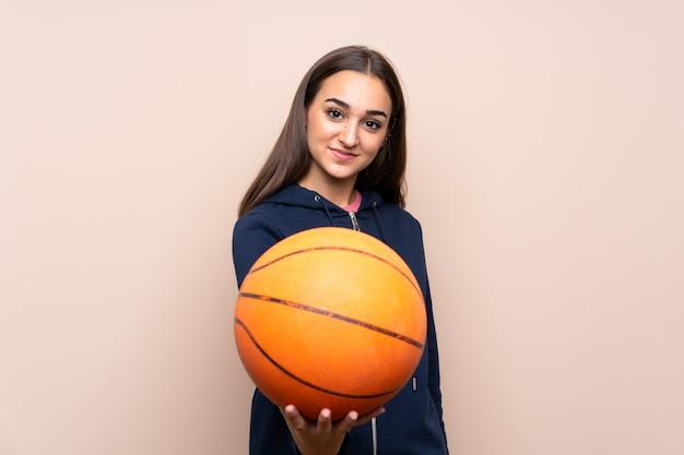 Jonge vrouw over geïsoleerde achtergrond met bal van basketbal