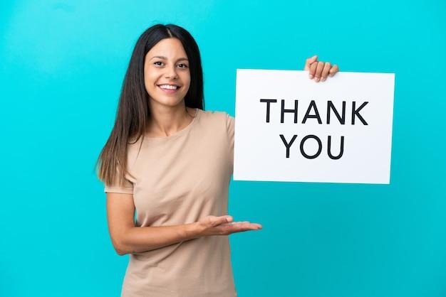 Jonge vrouw over geïsoleerde achtergrond met een bordje met de tekst bedankt en erop wijzend