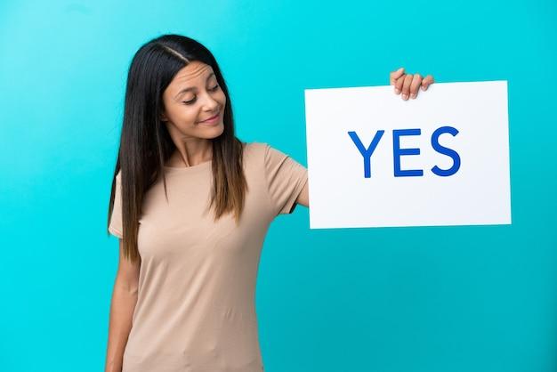 Jonge vrouw over geïsoleerde achtergrond met een bordje met de tekst yes