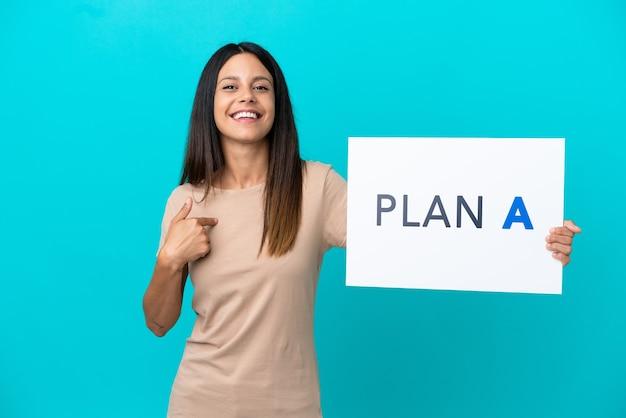 Jonge vrouw over geïsoleerde achtergrond met een bordje met het bericht plan a en erop wijzend