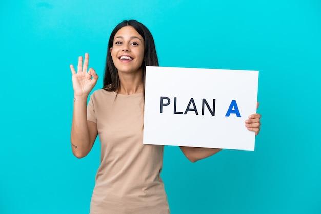 Jonge vrouw over geïsoleerde achtergrond met een bordje met het bericht plan a met ok teken