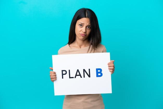 Jonge vrouw over geïsoleerde achtergrond met een bordje met het bericht plan b met droevige uitdrukking