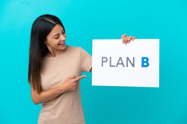 Jonge vrouw over geïsoleerde achtergrond met een bordje met het bericht plan b